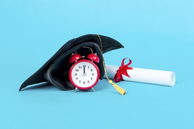 Tappo di laurea sull'orologio rosso vicino al diploma, immagine su sfondo blu, tempo di laurea di concetto