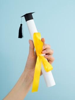 Diploma di laurea con nastro giallo e cappuccio accademico