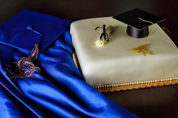 Torta fondente di laurea con cappello blu e abito su sfondo scuro.