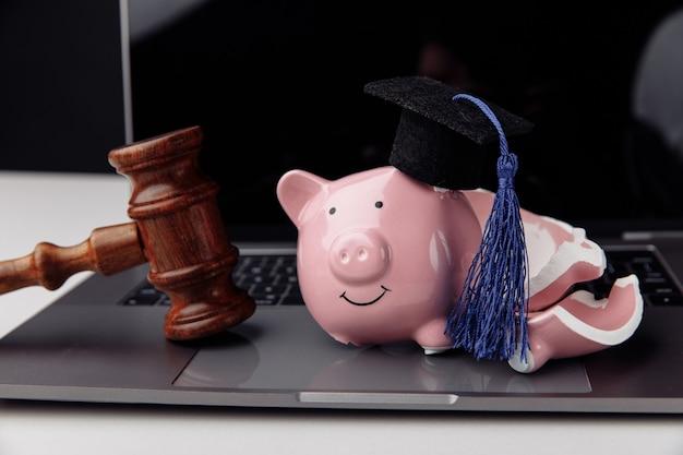 Cappello di laurea sul salvadanaio rotto su un computer portatile con martelletto. risparmiare denaro per il concetto di istruzione.
