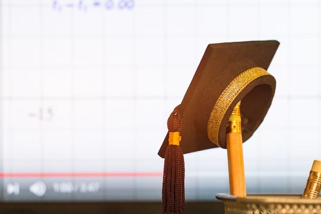 Cappello di laurea su matite con grafico di equazione aritmetica formula