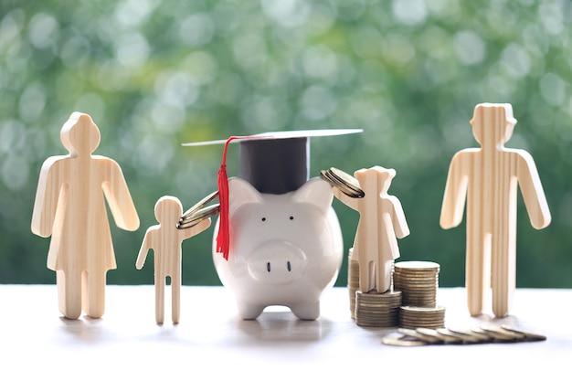 Cappello di laurea sul salvadanaio con famiglia modello e pila di monete soldi su sfondo verde naturale