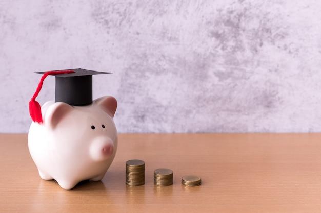 Cappello di laurea sul salvadanaio con pila di monete soldi sul tavolo, risparmiando denaro per il concetto di istruzione
