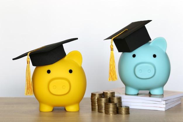 Cappello di laurea sul salvadanaio con pila di monete soldi su sfondo bianco, risparmio di denaro per il concetto di istruzione