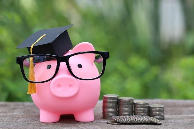Cappello di laurea sul salvadanaio rosa con una pila di monete soldi sullo spazio verde della natura