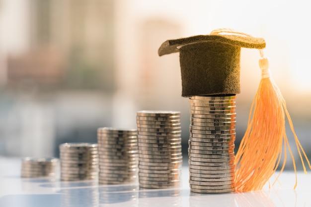Cappello di laurea in cima pila di monete.