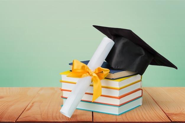 Tocco di laurea in cima alla pila di libri sullo sfondo
