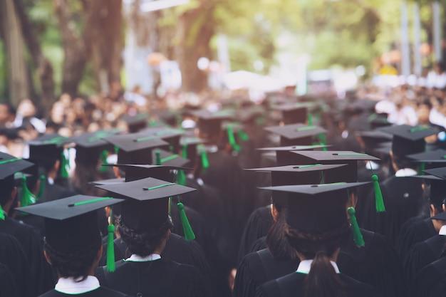 Laurea, studente tiene i cappelli in mano durante il successo di inizio laureati dell'università, congratulazioni per l'educazione del concetto.cerimonia di laurea, si congratula con i laureati all'università.
