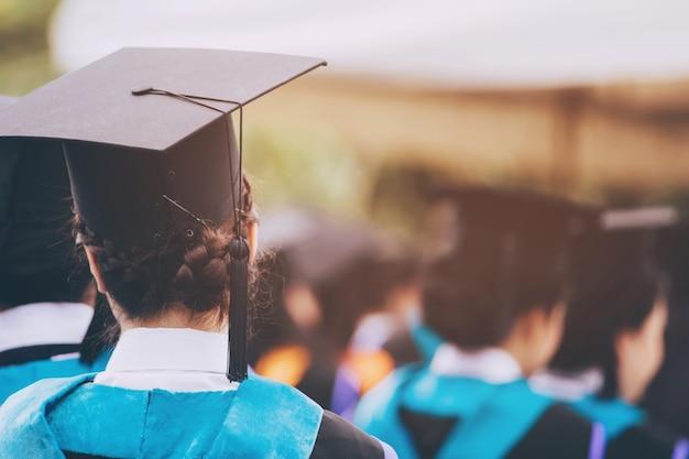 Laurea, studente tenere i cappelli in mano durante il successo di inizio laureati dell'università, congratulazioni per l'educazione del concetto
