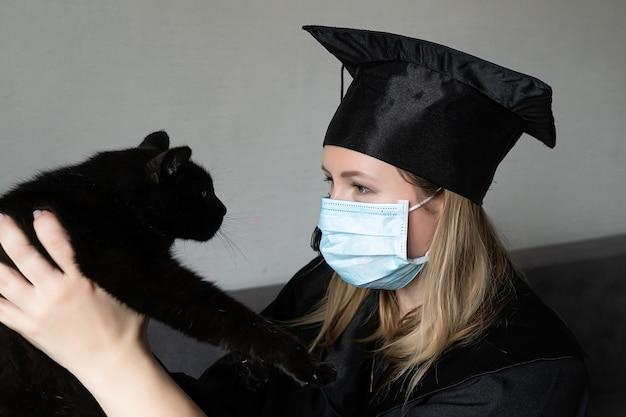 Laurea di una donna con maschera facciale vestita con un abito nero e con in mano un gatto nero