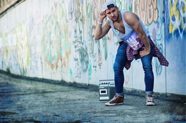 Muro di graffiti giovane con berretto