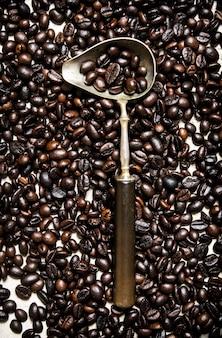 Chicco di caffè tostato in grani con un cucchiaio.