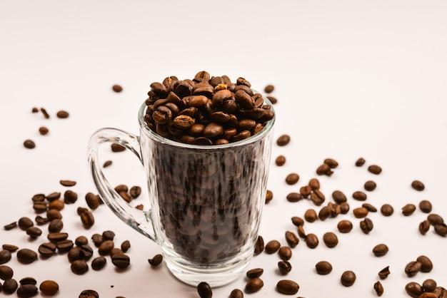 I chicchi di caffè vengono versati in una tazza di vetro su uno sfondo bianco