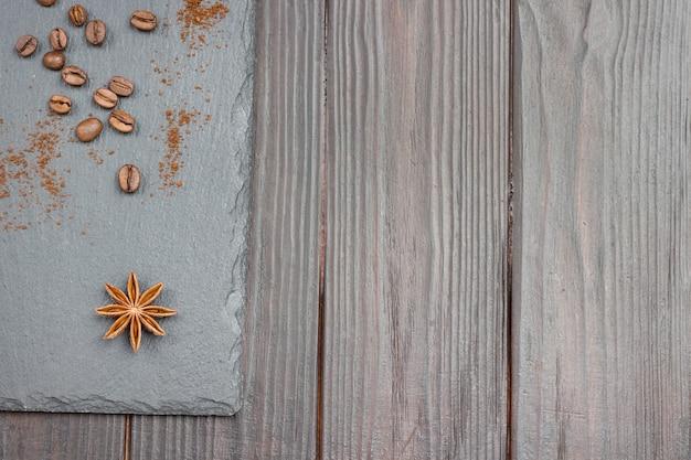 Chicchi di caffè, anice stellato e chicchi di caffè macinato su fondo nero. disposizione piatta. copia spazio