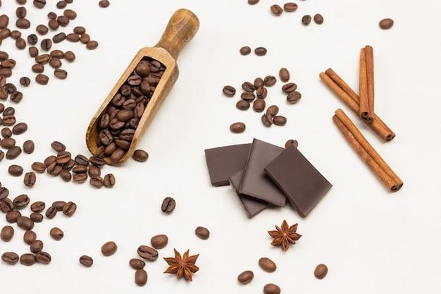 Chicchi di caffè in paletta di legno e sul tavolo. cioccolato, bastoncini di cannella e anice stellato. sfondo bianco. vista dall'alto
