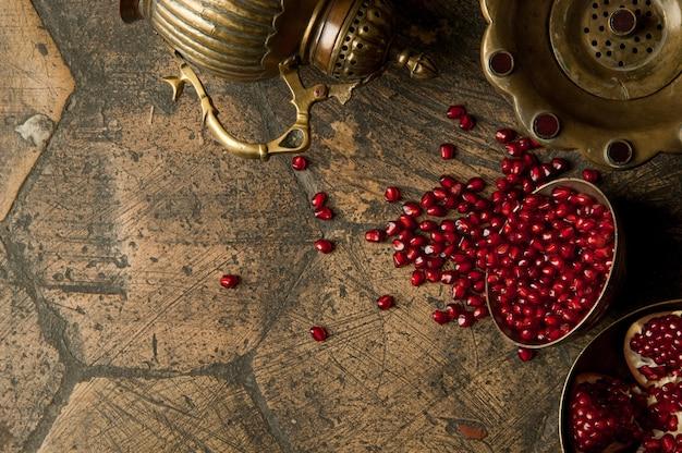 Chicchi e semi di melograno con una brocca di rame su un vecchio selciato decorativo