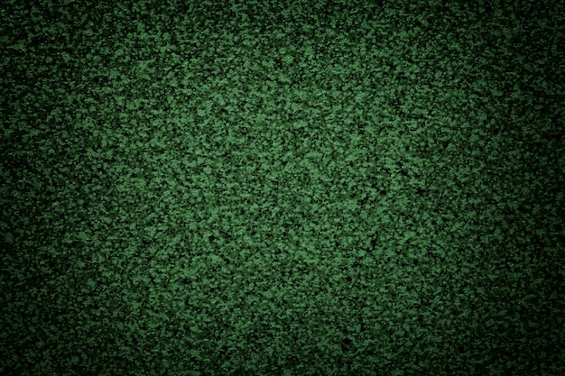 Sfondo verde granuloso del piano del tavolo con vignetta scura. texture superficie astratta con motivo a piccole briciole