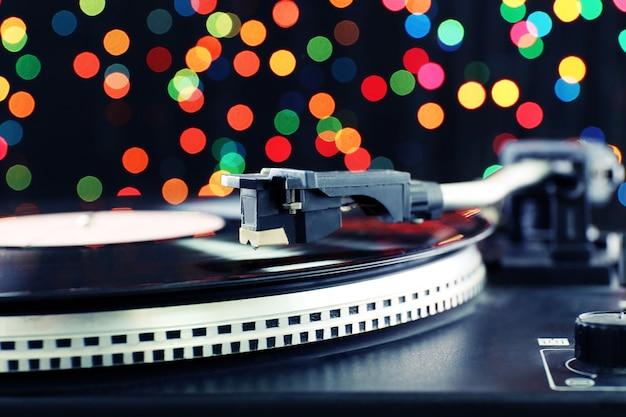 Grammofono con un disco in vinile su sfocato colorato