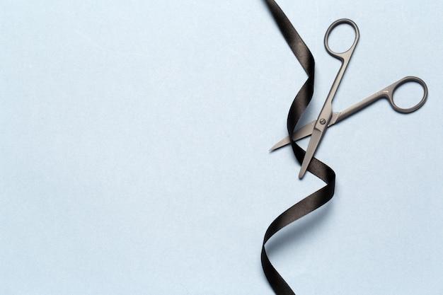 Grande apertura illustrata con le forbici e un nastro nero