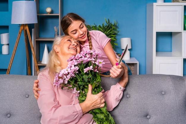Nipote che presenta fiori alla nonna a casa, momenti felici della vita domestica