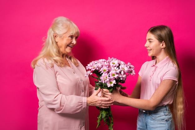 Nipote che presenta fiori alla nonna