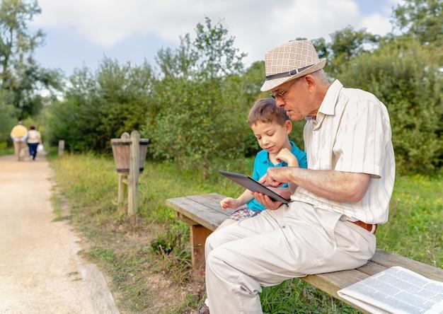 Nipote che insegna a suo nonno a usare una tavoletta elettronica su una panchina del parco. concetto di valori di generazione.