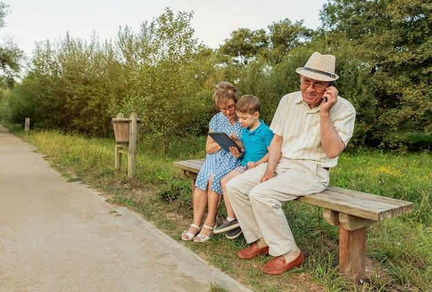 Nipote che insegna a sua nonna a usare una tavoletta elettronica su una panchina del parco. concetto di valori di generazione.