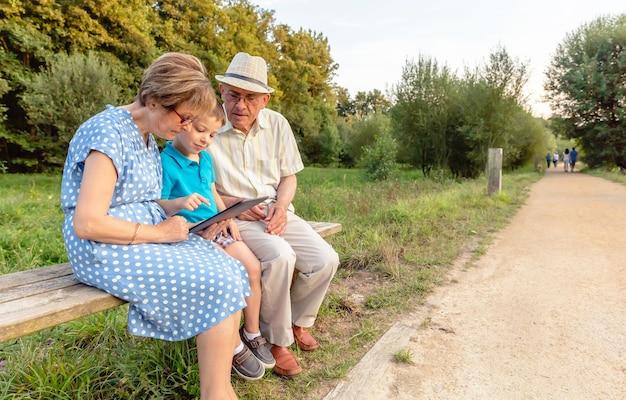 Nipote che insegna ai nonni a usare una tavoletta elettronica su una panchina del parco. concetto di valori di generazione.
