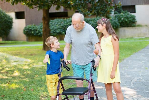 I nipoti accompagnano il nonno a camminare aiutandolo