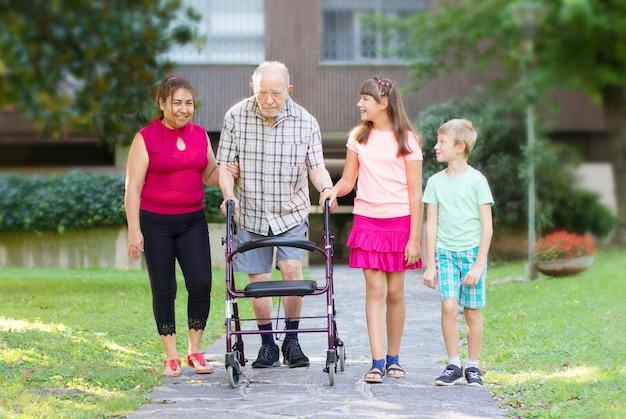 Nipoti e badante accompagnano il nonno a camminare aiutandolo