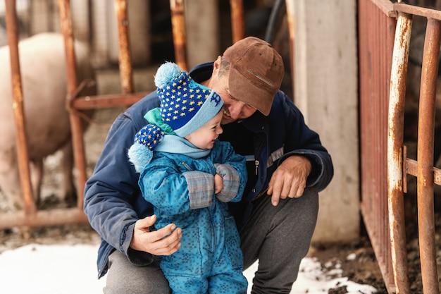 Il nonno si inginocchia e fa ridere suo nipote. entrambi indossano abiti invernali.
