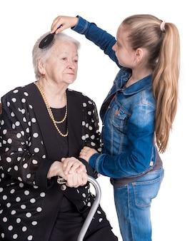 Nipote che pettina i capelli sua nonna su un muro bianco