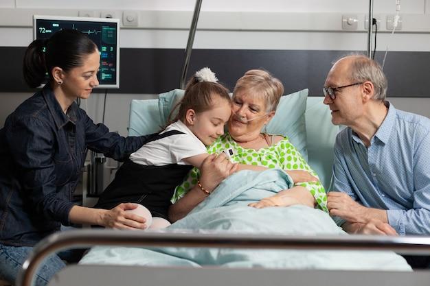 Nipote che abbraccia la nonna anziana malata che la visita nel reparto ospedaliero