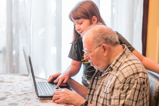 La nipote sta aiutando il nonno a usare un pc Foto Premium