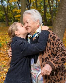 Nipote che bacia la nonna nel parco d'autunno