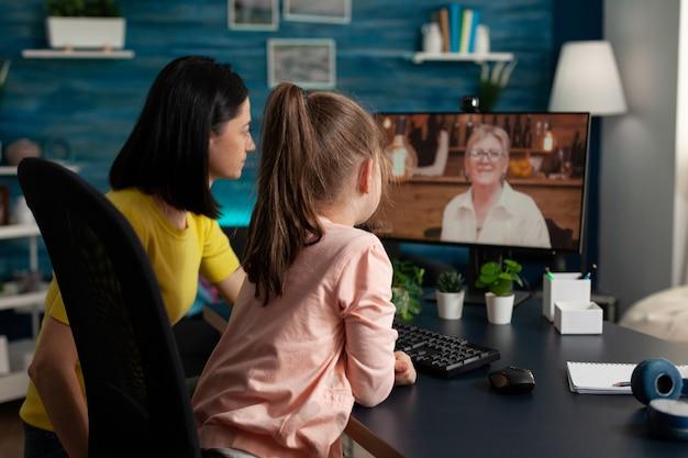 Nipote seduta accanto al genitore che parla con la nonna in pensione d