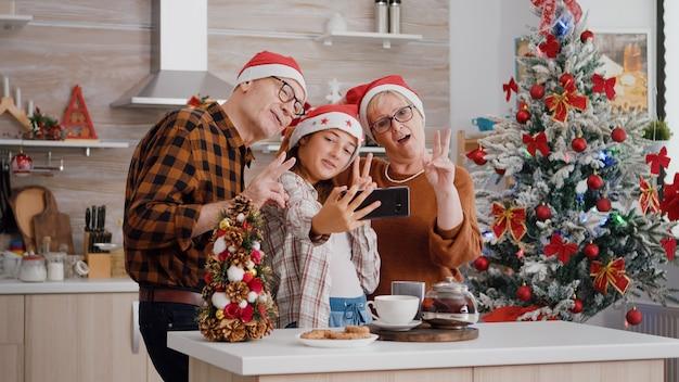 Nipote che prende selfie usando lo smartphone con i nonni durante la celebrazione delle vacanze di natale