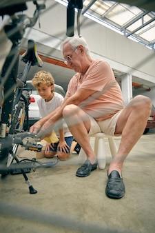 Nonno che fissa la bicicletta per il nipote sul parcheggio