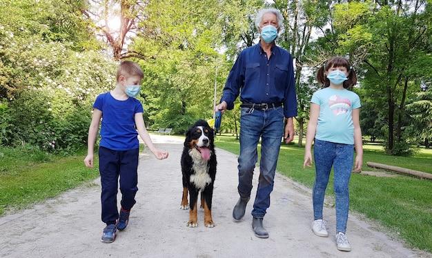 Nonno e nipote stanno passeggiando nel parco con il cane durante la pandemia di coronavirus