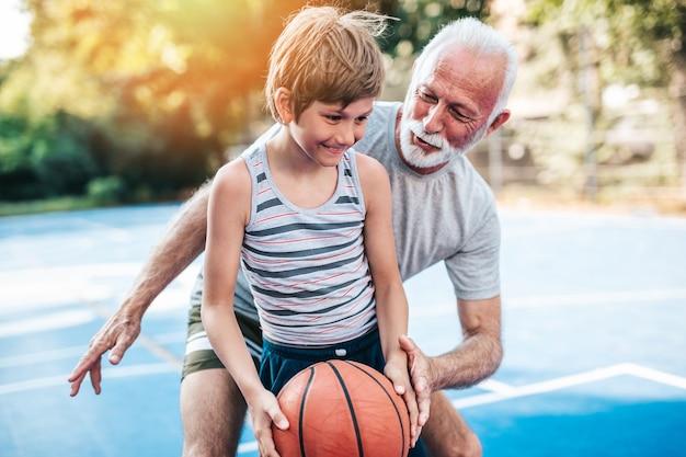 Nonno e nipote che giocano a basket.