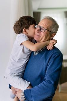 Nonno che tiene il suo nipote vicino alla finestra