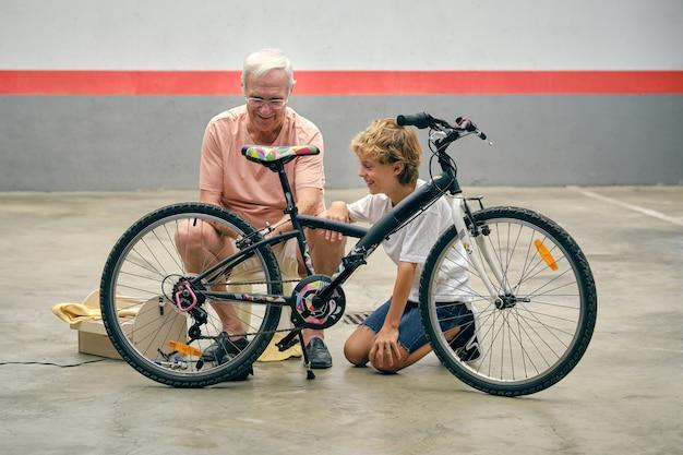 Nonno che insegna al ragazzo ad aggiustare la bicicletta