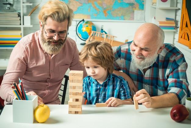 Nonno che insegna al nipote come giocare ai giochi jenga ritratto multigenerazionale maschile