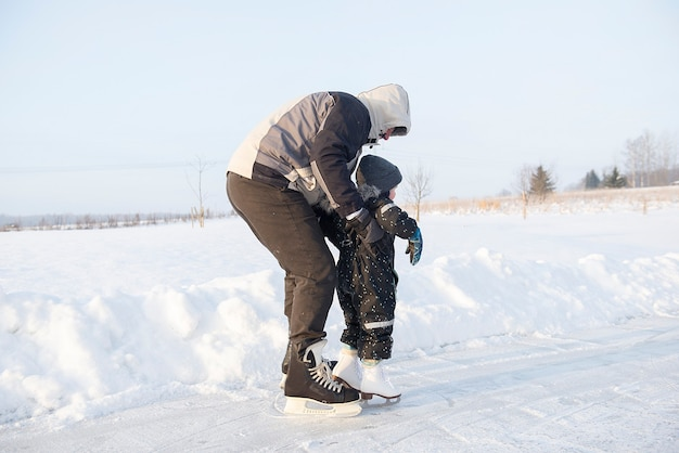 Nonno che insegna al suo nipotino a pattinare sul ghiaccio alla pista di pattinaggio all'aperto
