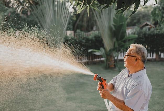 Il nonno innaffia le piante in giardino da solo. stile di vita in età pensionabile sul cortile di casa.