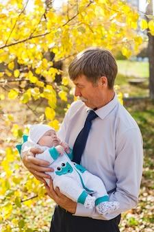 Nonno con un bambino, un bambino cammina in autunno nel parco o nella foresta. foglie gialle, la bellezza della natura. comunicazione tra un bambino e un genitore.