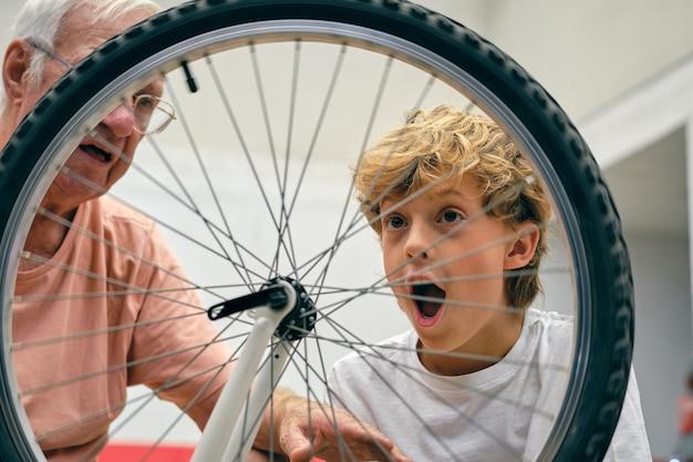 Nonno con il nipote eccitato che ripara la bicicletta