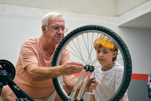 Nonno con il nipote che ripara la bicicletta