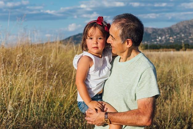Nonno con la nipote in braccio al tramonto al tramonto