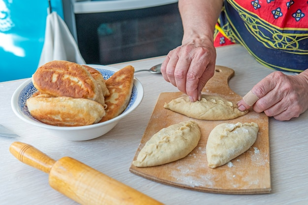 La nonna cucina le torte. cibo cucinato in casa. torte di pasta fatta in casa nelle mani delle donne. il processo di fare l'impasto della torta a mano